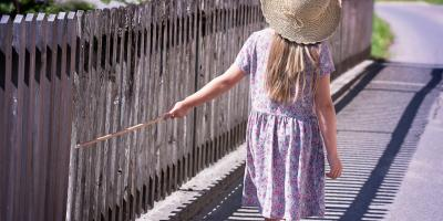 Image of a child walking down a fence